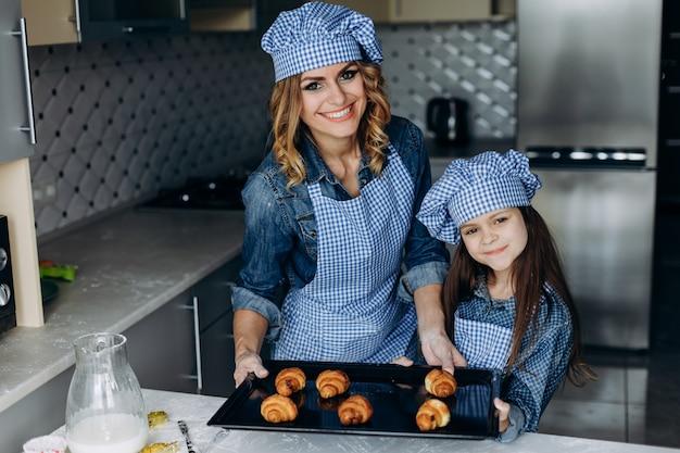 娘と母親は、クロワッサンを焼きました。家族の概念