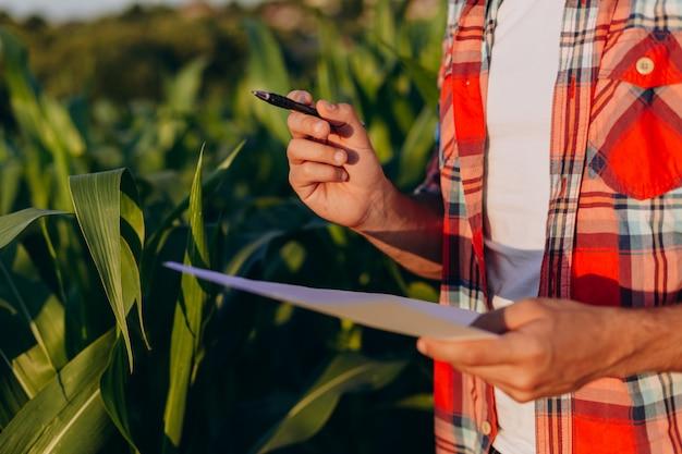 ペンを持っているクローズアップ男性手。収穫量を管理する農学