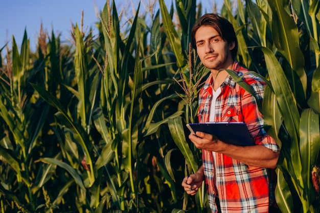 トウモロコシ畑に立って、カメラを見て幸せな農学者の肖像画。