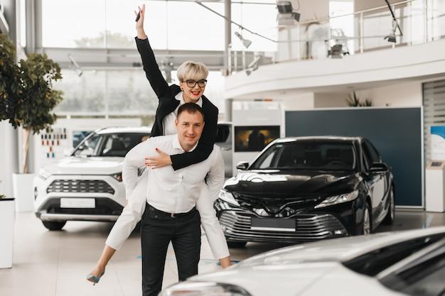 車を買うカップル。カーサロンでペアを組んで自動車を選ぶ