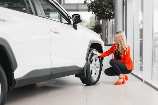 白い車の隣に座って、ホイールに触れる女性。
