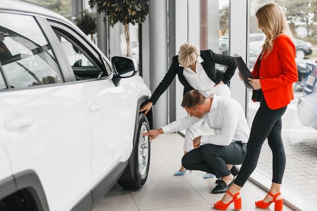 ホイールに触れて、それを注意深く見て車の隣のカップル。妻と夫は自動車を選ぶ