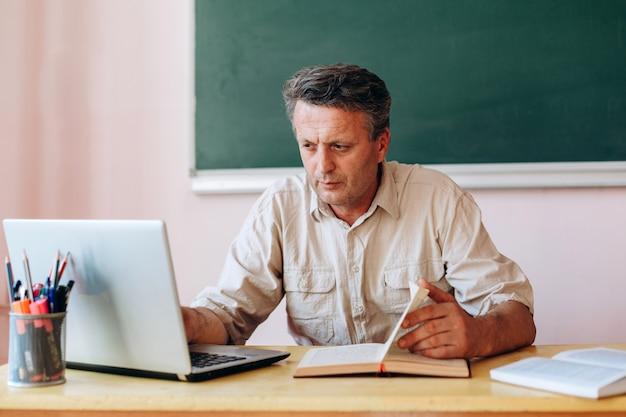 開いている教科書とラップトップで座っていると作業中年教師。
