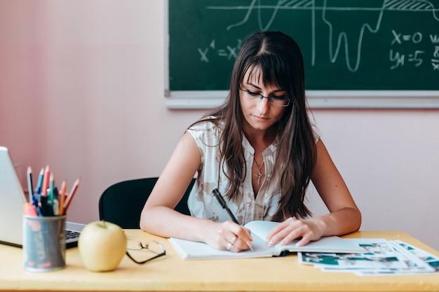 テーブルに座って書くメガネの女教師。