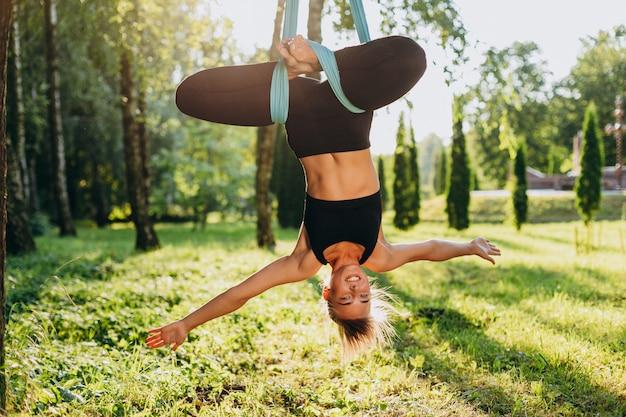 魅力的な女性は木の頭でフライヨガを練習します。コンセプトヨガ