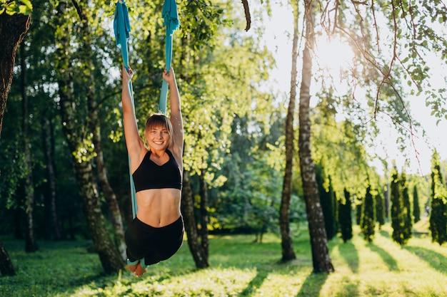 Счастливая девушка делает летать йоги на открытом воздухе. поза с отклонением.