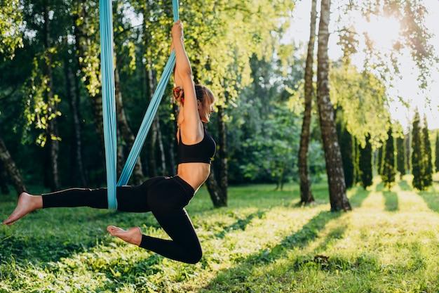 屋外の公園でフライヨガをやっている女性。側面図