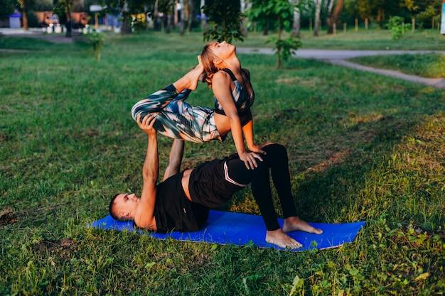 男と女が屋外の公園で一緒にヨガをやっています。