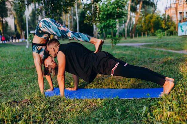 男と女が屋外の公園で一緒にヨガをやっています。男は女性にキス