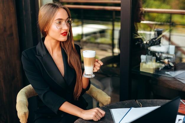 Портрет блондинка предприниматель в очках, держа чашку кофе и смотрит прямо