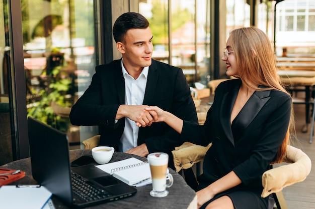 男と女が手を振る。商売上の取引