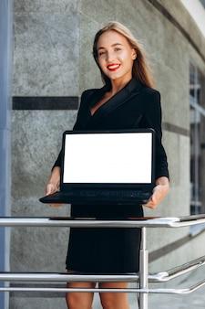Женщина держит пустой макет белый экран ноутбука.- изображение