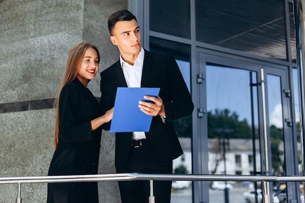 ビジネスパートナーの男性と女性の隣に立っているドキュメントとビジネスビル。-画像