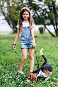 Улыбающаяся маленькая девочка, стоящая с собакой и смотрящая на камеру