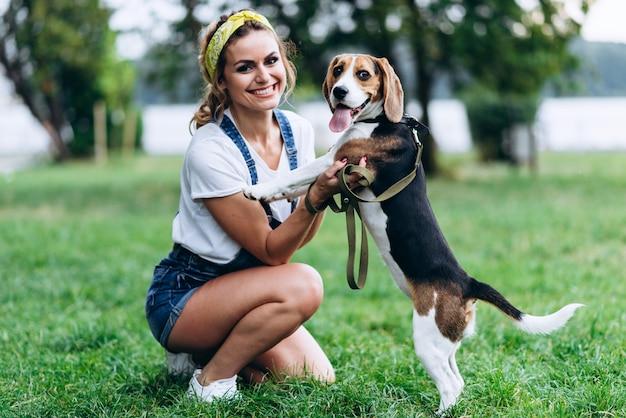 Счастливая женщина играет с собакой и смотрит в камеру. -образ