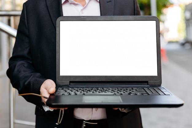Изображение крупного плана бизнесмена держа открытый компьтер-книжку, пустой белый пустой экран
