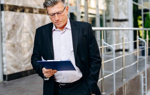 Старший бизнесмен в очках, внимательно читая документ