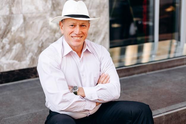 シャツと帽子の舗装の上に座って年配の男性の肖像画は、手を組んでください。