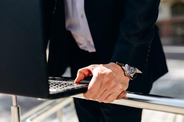 ノートパソコンのキーボードの男性の手をクローズアップ。