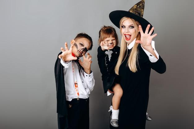 怖いジェスチャーを示すデザインの凝った服の家族