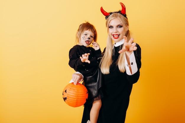 黄色に対して立っていると小さな女の子を保持している幸せな感情の悪魔の女性