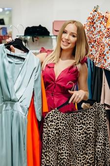 ドレスとブラウスを選択して保持している美しい、スタイリッシュな女の子