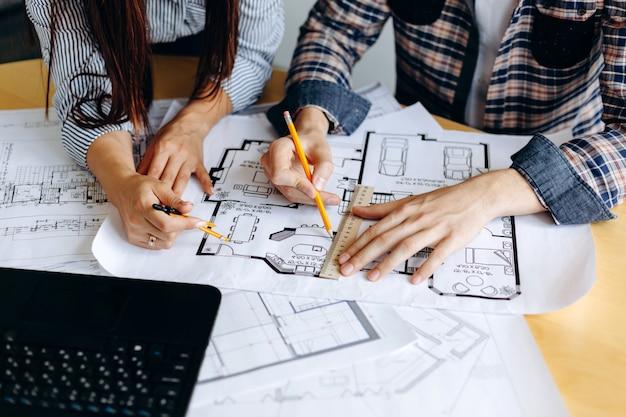 オフィスのテーブルの設計図を見て建築家