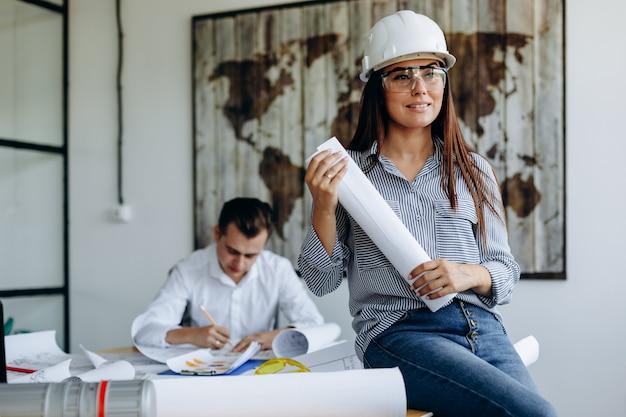 メガネとヘルメットの建築家の若い女性建築家は同僚と一緒にオフィスで働いています