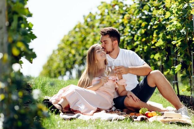 ブドウ園でピクニックを持っている若いカップルを愛しています。