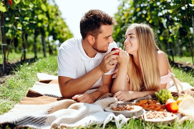Влюбленная молодая пара лежит на плед в виноградной лозе