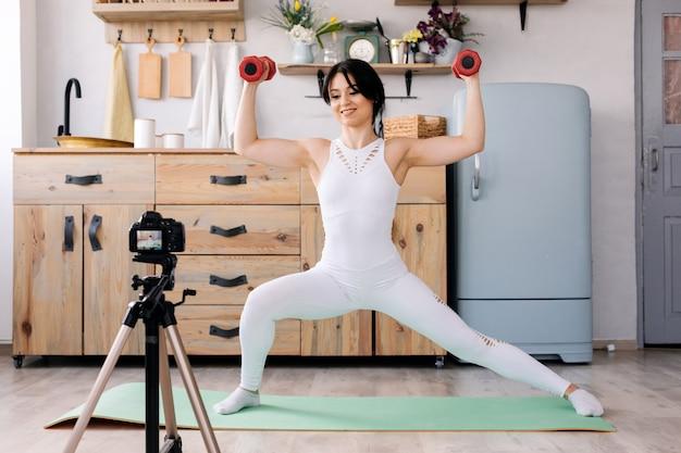 Онлайн обучение. радостная молодая женщина делает упражнения во время записи видео тренировки