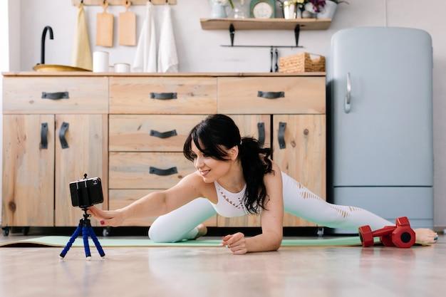 Молодая спортсменка делает ногу на спортивный коврик