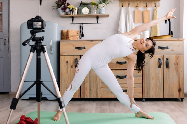 Красивая девушка в спортивной одежде занимается йогой и снимает видео для своего блога