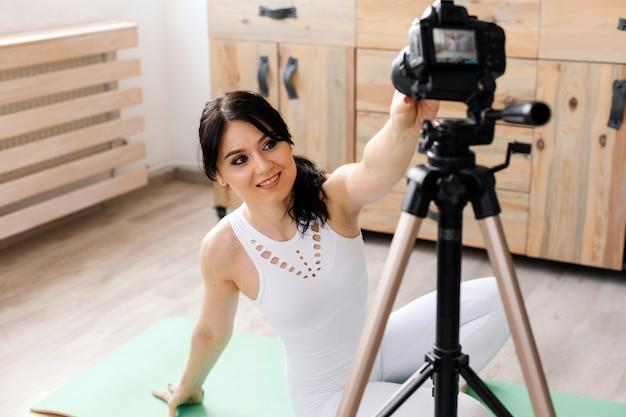 自宅でスポーツビデオを記録する若い女性ブロガー