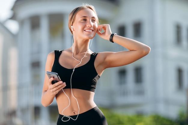 スマートフォンを保持しているイヤホンで黒のスポーツウェアで幸せな女の子。