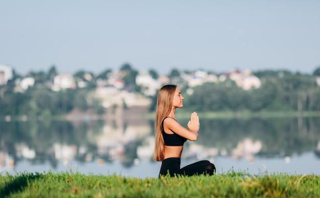 瞑想に座っている女性は、彼女の手からジェスチャーナマステと屋外ポーズします。側面図