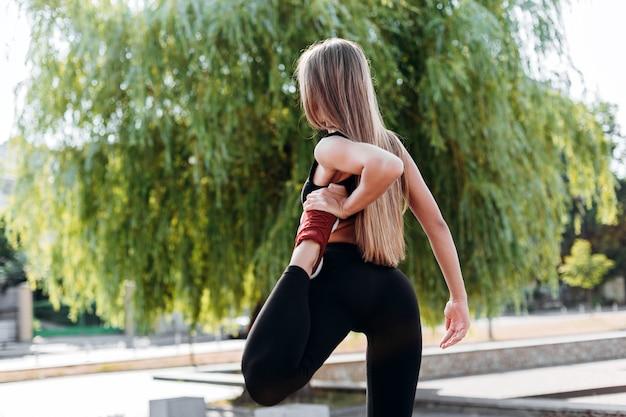 足を保持している彼女の足の手を伸ばす少女。背面図