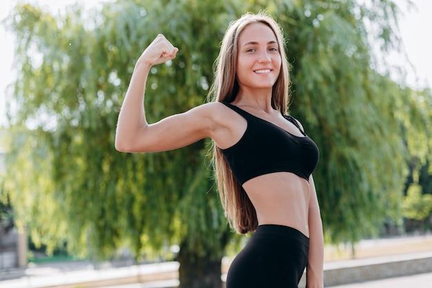 手の筋肉を示すとカメラを見て金髪のスポーティな女の子。