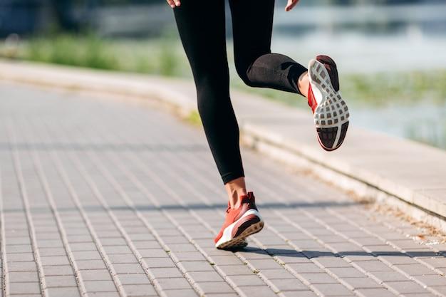 屋外の女性ランナーの足をクローズアップ。