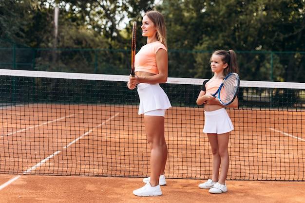 母と娘はテニスをする準備をしています
