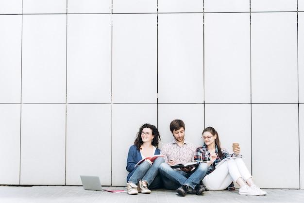 壁の近くの床に座って本やガジェットを持っている人。教育ソーシャルメディアのコンセプト。