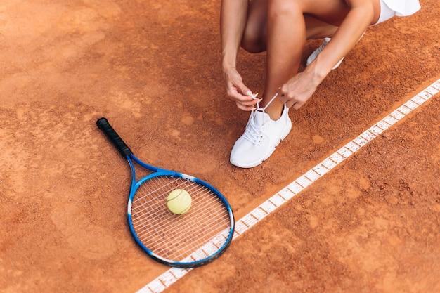 Нога спортсмена возле теннисной ракетки и мячей
