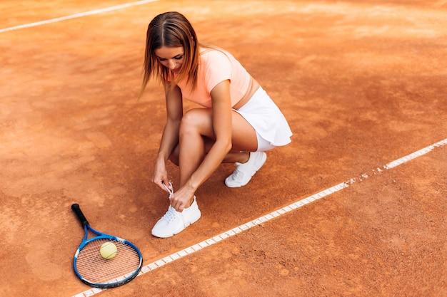 Концепция тенниса с мячом, сеткой, ракеткой и женщиной на открытом воздухе на корте