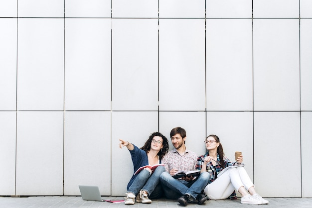 若い人たちは、テキストのために自由空間に現れ、笑顔で壁の近くに座っています。学生は勉強しています。教育ソーシャルメディアのコンセプト。
