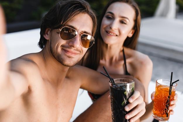 Улыбающаяся пара делает селфи и держит коктейли на пляже