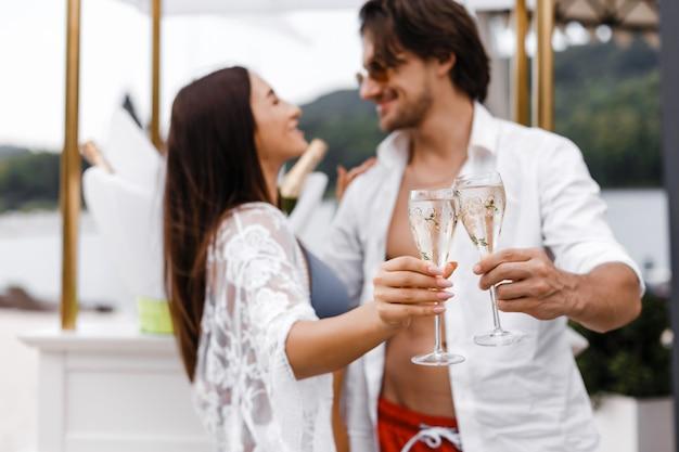 ロマンチックなカップルは屋外でワイングラスを乾杯