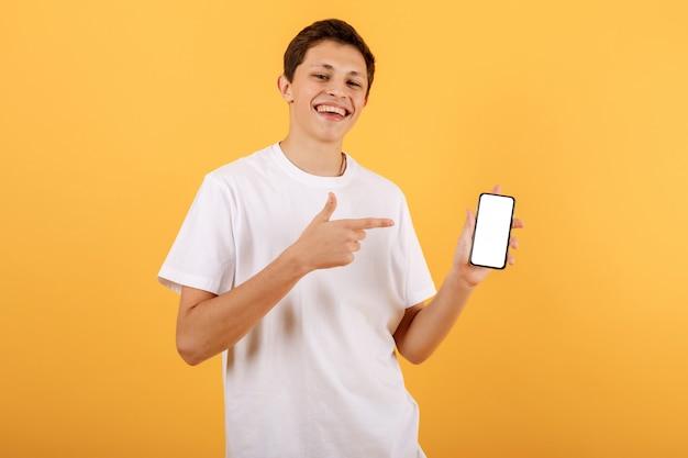 Удивленный мальчик в белой футболке на оранжевом фоне