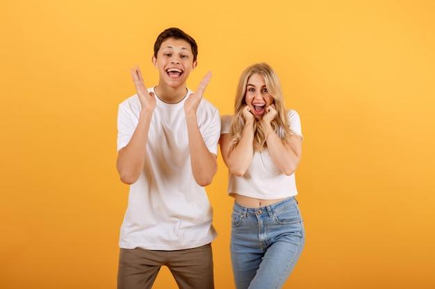 Удивленная улыбающаяся молодая пара, два друга, парень и девушка в белых футболках, позируют на желто-оранжевом фоне.