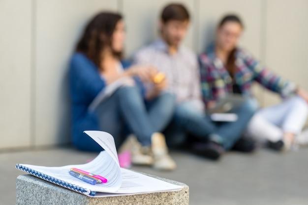 壁の近くの床に座っている本やガジェットを持つ人々のぼんやりした写真。教育ソーシャルメディアのコンセプト。
