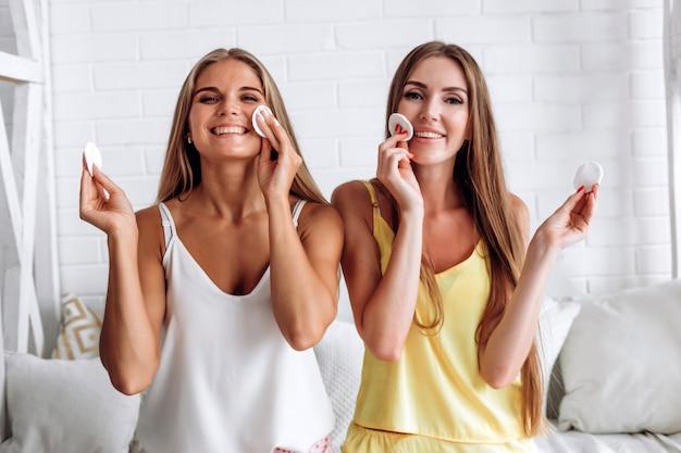 Молодые женщины с ватными подушками возле лица. уход за кожей, спа и косметические процедуры. удаление макияжа